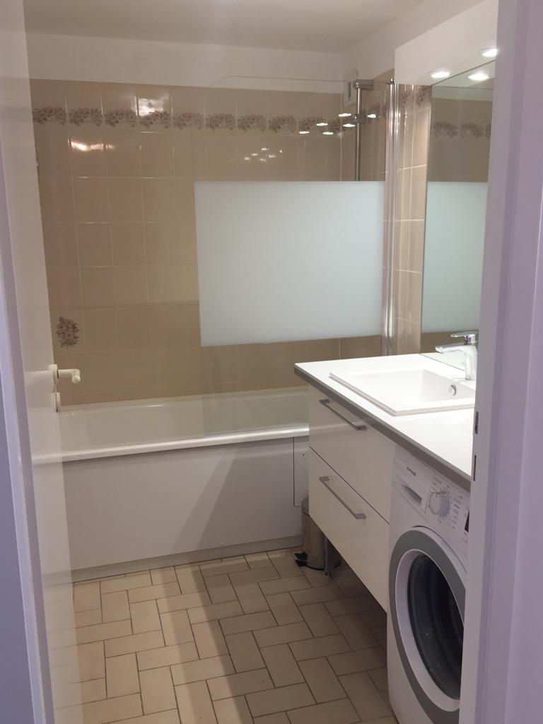 salle de bain avec lave linge et baignoire